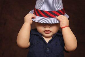 赤ちゃんが帽子で目を隠す
