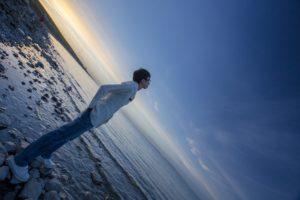 男性が海で黄昏ている