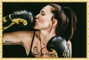 女性がボクシンググローブにキスしている