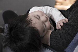 抱きかかえられて、寝ている子供